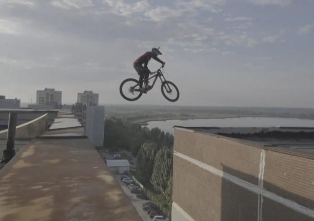 乌拉尔学生骑车在多层建筑物的屋顶之间跳跃