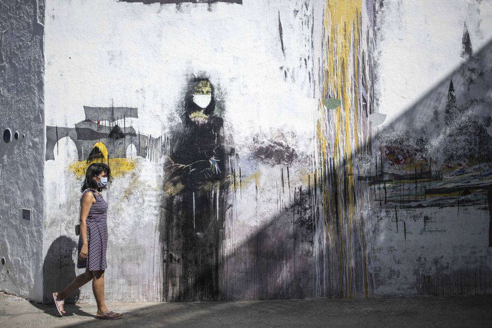 摩洛哥一名戴口罩的女孩在一副画着戴口罩的蒙娜丽莎涂鸦前