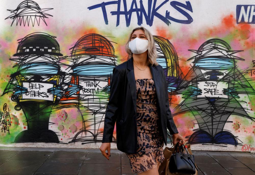 伦敦一名戴口罩的女孩在涂鸦墙前