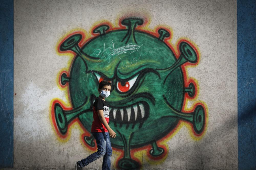 加沙一名男孩走过画着新冠病毒的涂鸦墙