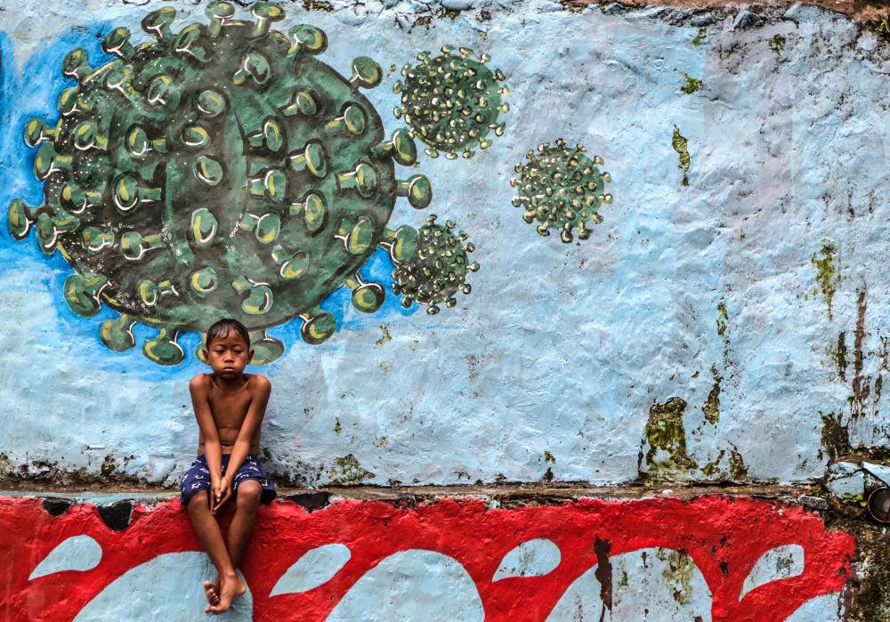 西爪哇茂物市一名男孩坐在涂鸦墙前