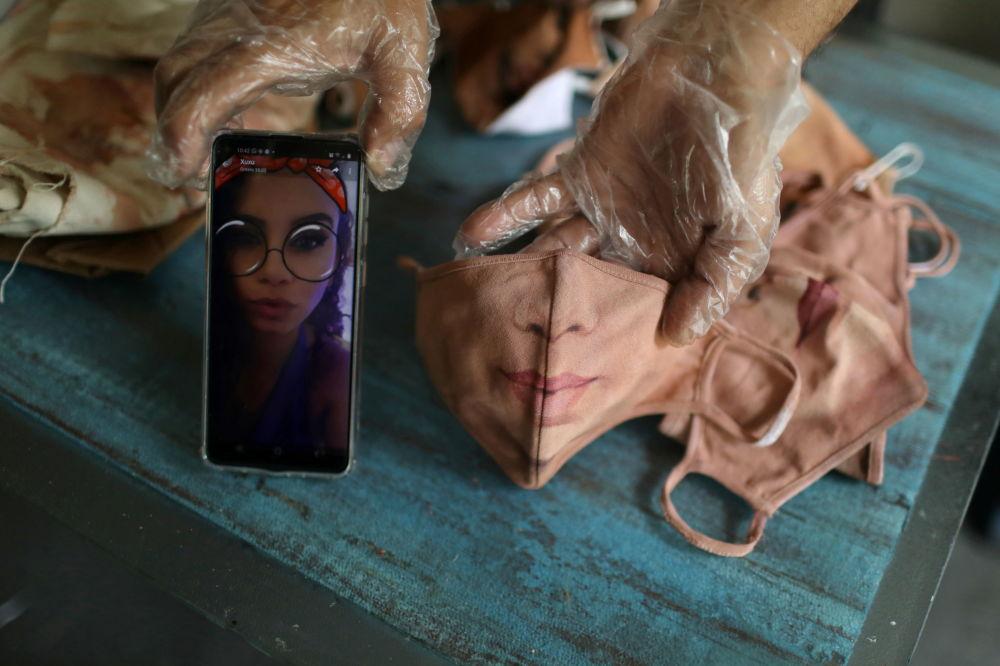 巴西画家豪尔赫•席尔瓦•罗里兹展示按手机上的女士照片创作的口罩绘画作品