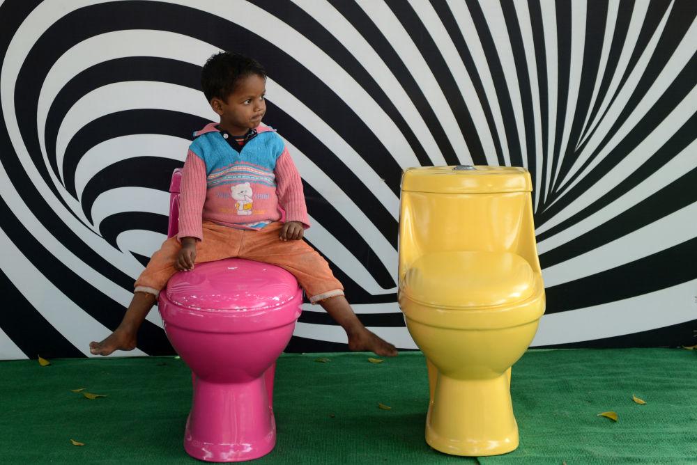 """在世界厕所日之际,在新德里举行的""""厕所是美丽的""""活动中,一个印度小男孩在上厕所"""