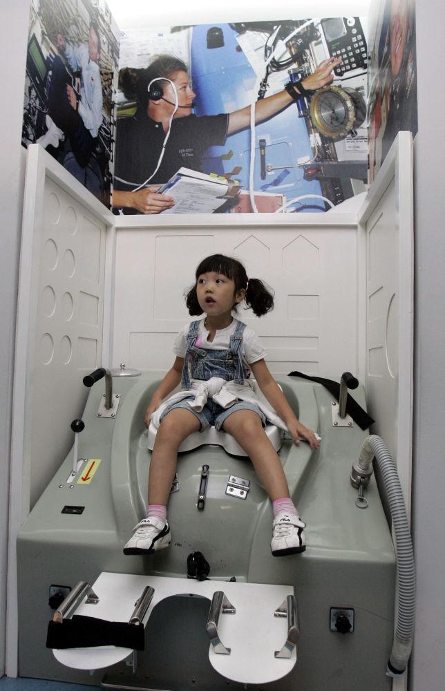 """韩国首尔,在""""太空体验""""展览上,一个小女孩在""""太空船厕所""""里"""