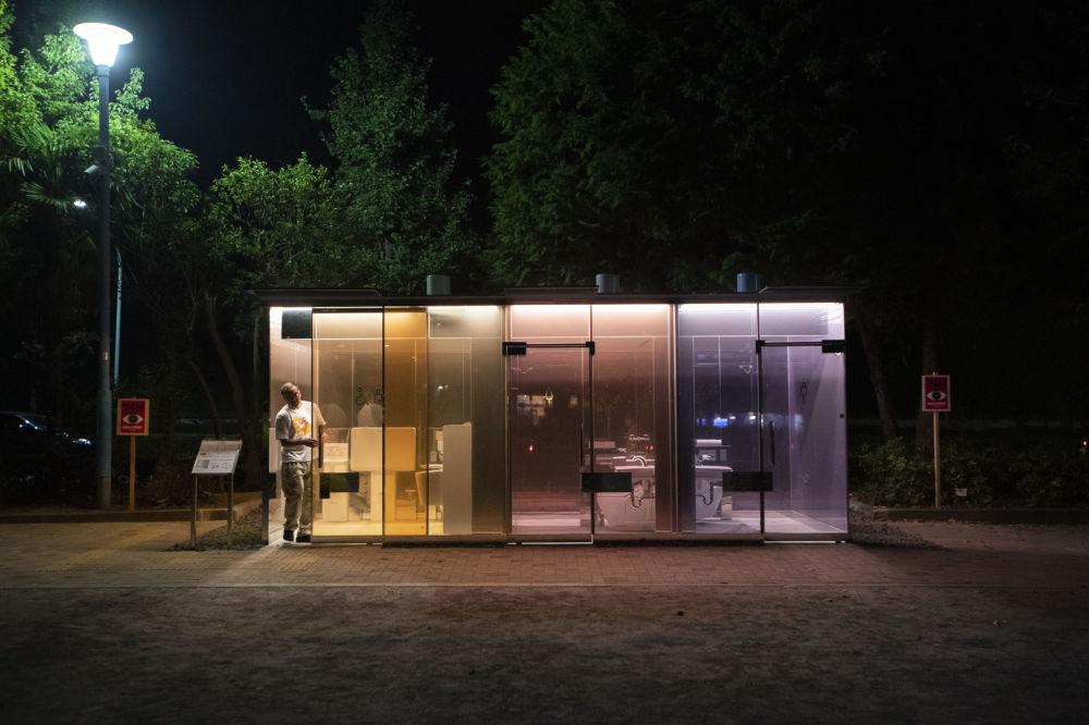 东京代代木迷你公园,公共厕所透明玻璃旁的男子