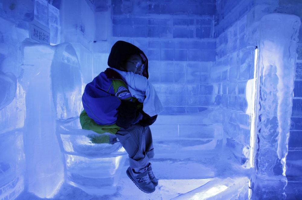 """韩国首尔,在""""冰之画廊""""展览上,一个小男孩在冰马桶上"""