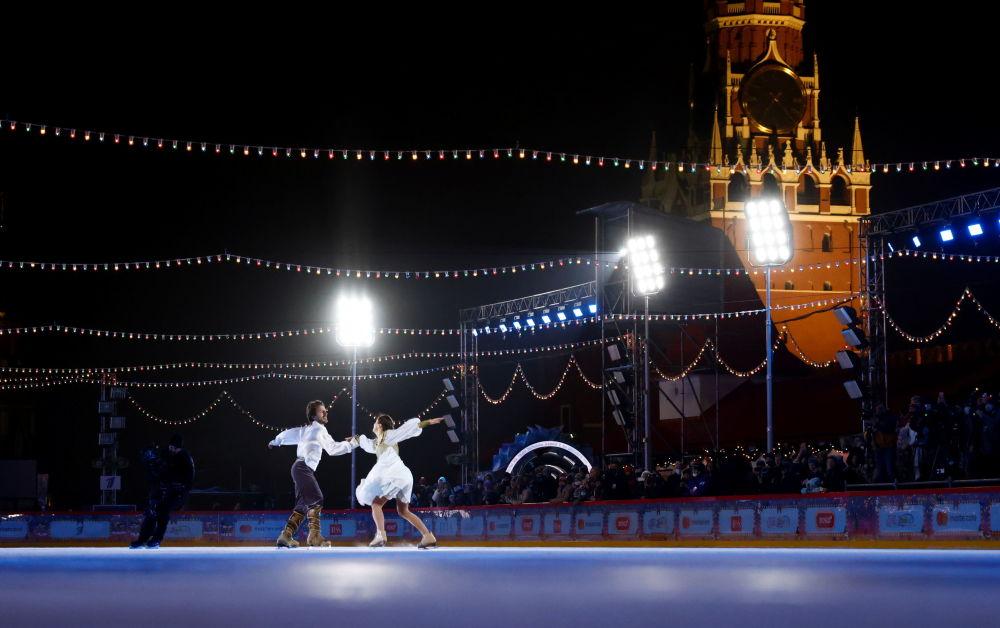花样滑冰女将玛格丽特·德罗比亚茨科和波利拉斯·瓦纳加斯在红场上的古姆溜冰场新溜冰季启动仪式上表演