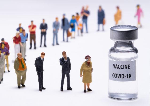 """写有""""新冠疫苗""""字样的小瓶旁的人物"""