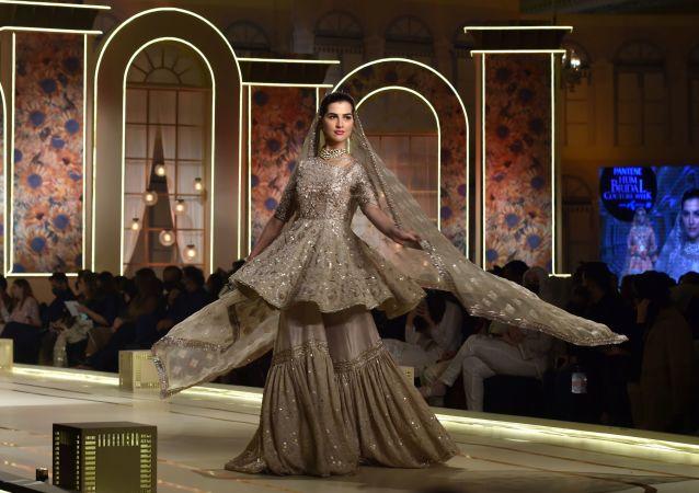模特身着Ayesha and Usman Ali婚礼服饰在婚礼时装周走秀环节展示。