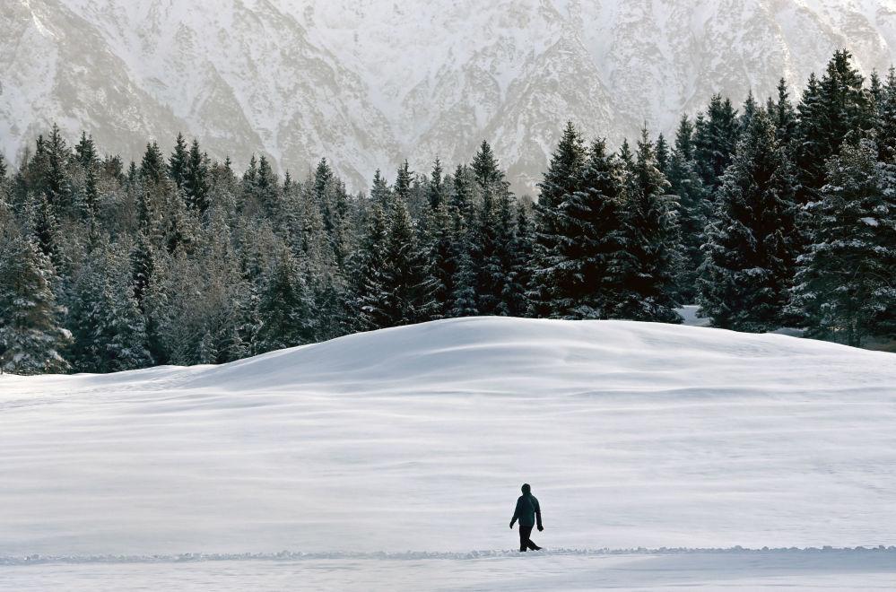 德国德国加米施-帕滕基兴市居民在雪地中穿行。