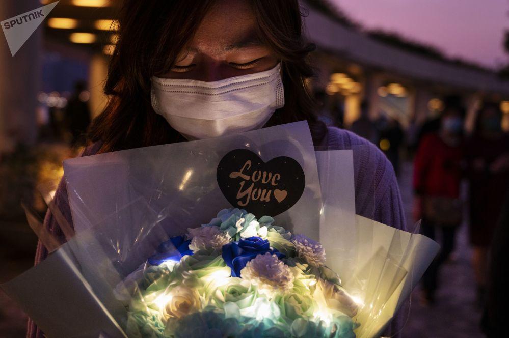 香港少女在维多利亚湾手捧玫瑰花。
