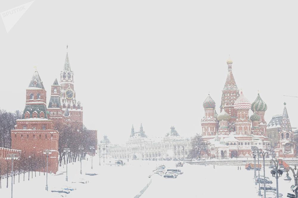雪中的莫斯科圣瓦西里升天大教堂和克里姆林宫的塔楼。
