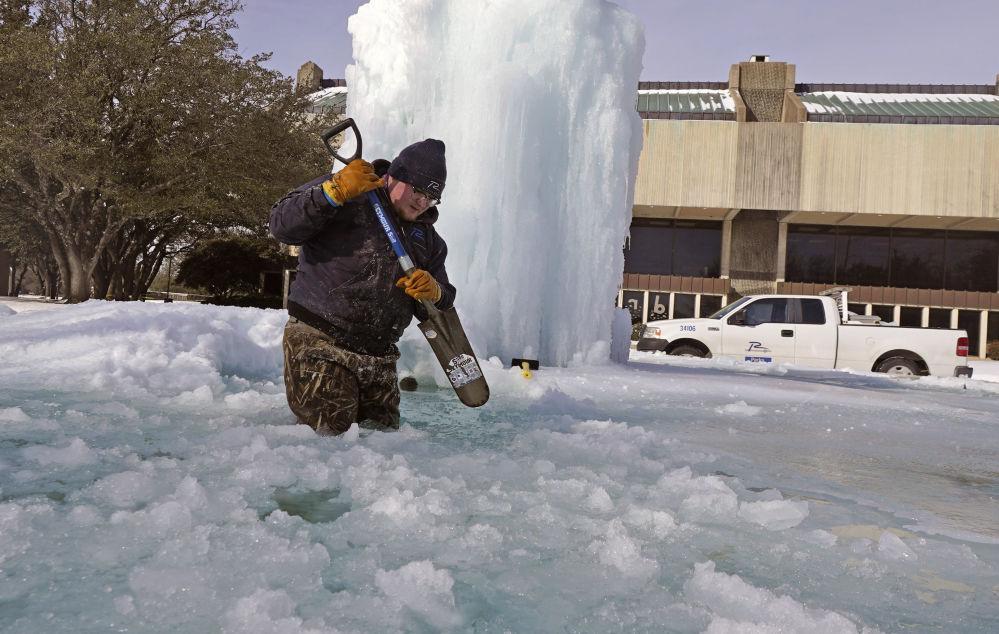得州理查森,一名工人在冰冻的喷泉里把冰打碎。