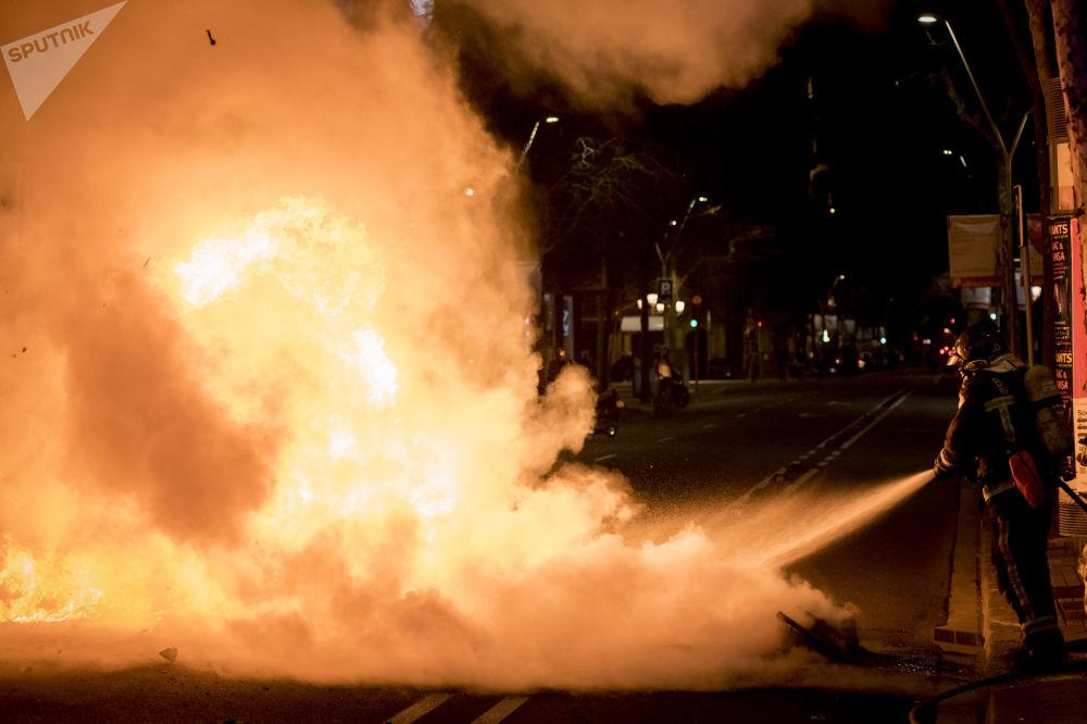 巴塞罗那,消防员扑灭了街上正在焚烧的摩托车,那里正在举行支持说唱歌手哈塞尔的示威活动。