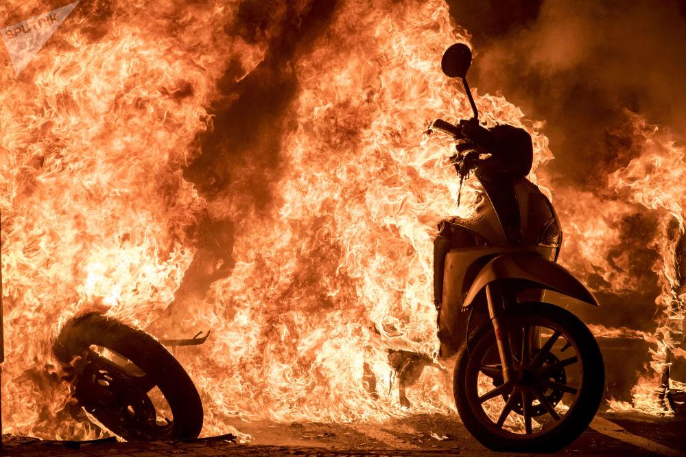 巴塞罗那的一条街上正在焚烧的摩托车,那里正在举行支持说唱歌手哈塞尔的示威活动。