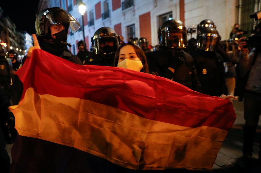 西班牙马德里,支持说唱歌手哈塞尔的示威活动期间,一个姑娘身披西班牙国旗。