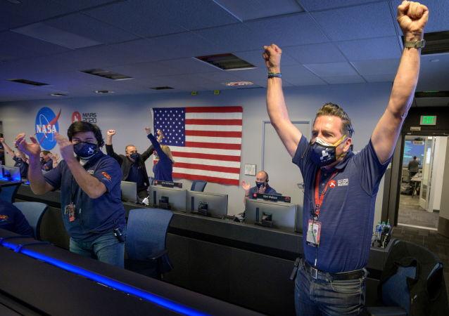 """美国宇航局工作人员收到""""毅力号""""火星探测器成功登陆的确认信息后,纷纷起立举手欢呼。"""