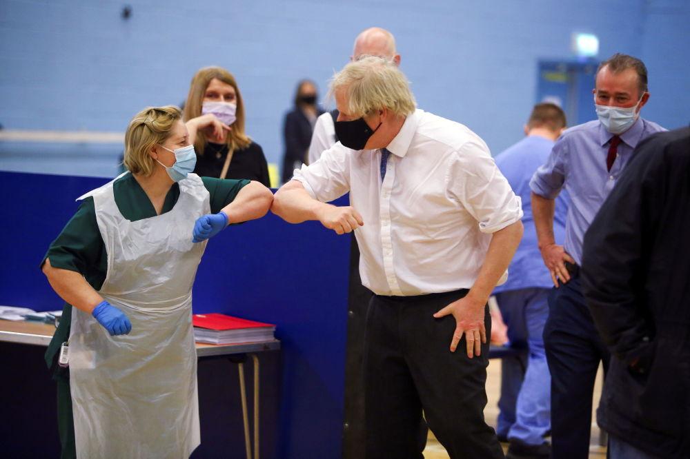 英国首相约翰逊在康布拉镇新冠疫苗接种中心致敬值守女护士。
