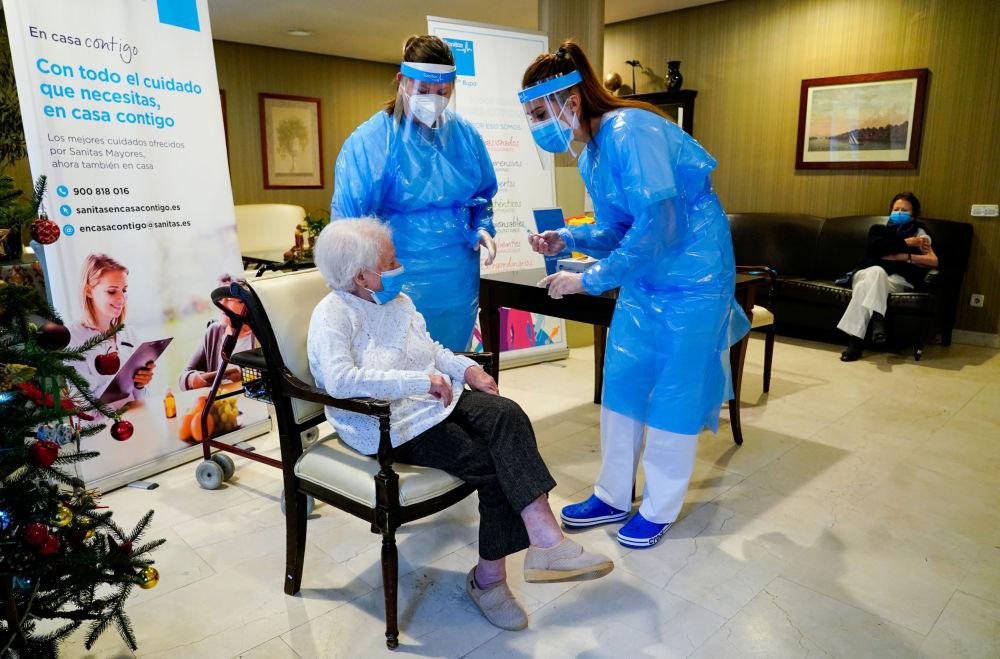 西班牙马德里敬老院工作人员陪护感染老人接种疫苗。
