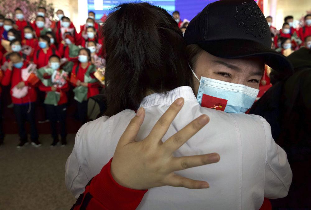 中国女医师在武汉天河机场与抗疫战友道别。