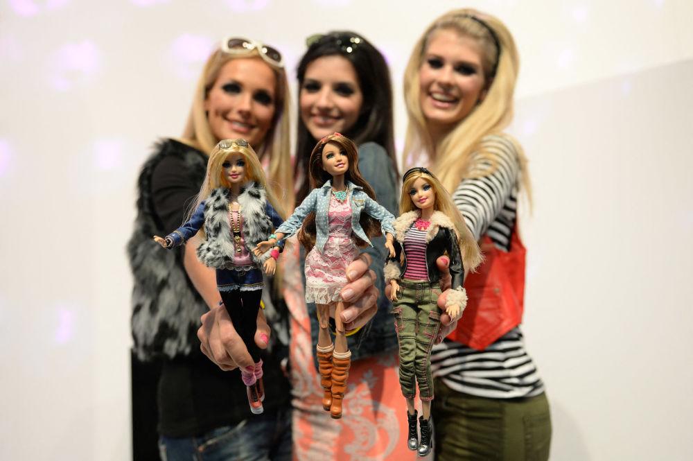 在纽伦堡国际玩具展的美泰公司的展台上,模特与穿着相似服装的芭比娃娃合影。