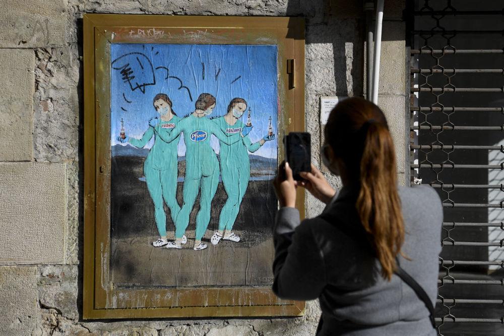 巴塞罗那,意大利街头艺术家TvBoy的涂鸦《三种疫苗》,俨如拉斐尔的名画《美惠三女神》。