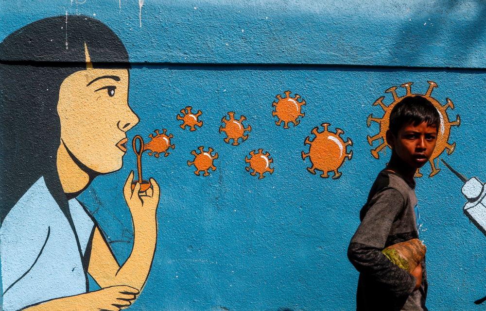 印度孟买,一个男孩从涂鸦前走过。