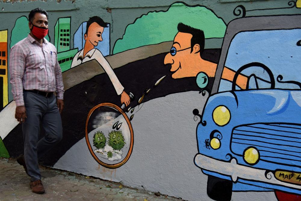 印度孟买,行人从以冠状病毒为主题的涂鸦墙前走过。