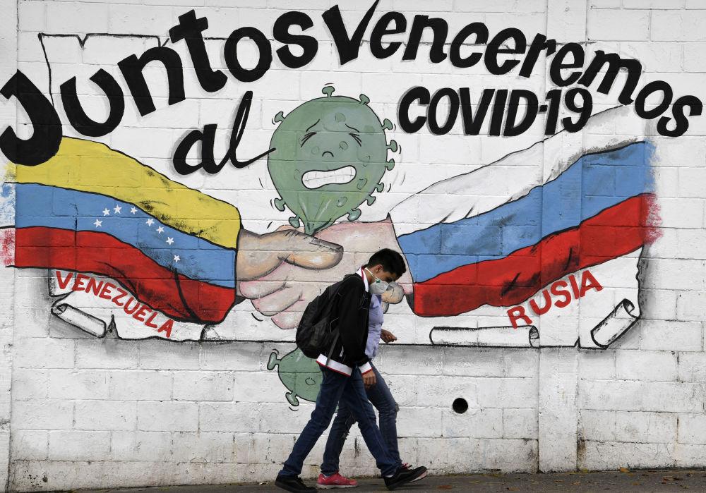 """委内瑞拉加拉加斯,绘有委内瑞拉和俄罗斯的国旗、上面写着""""我们将携手战胜新型冠状病毒""""标语的涂鸦。"""