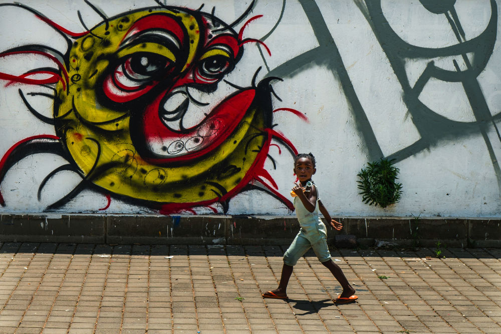 南非索韦托,一个孩子站在绘有新型冠状病毒的涂鸦墙前。