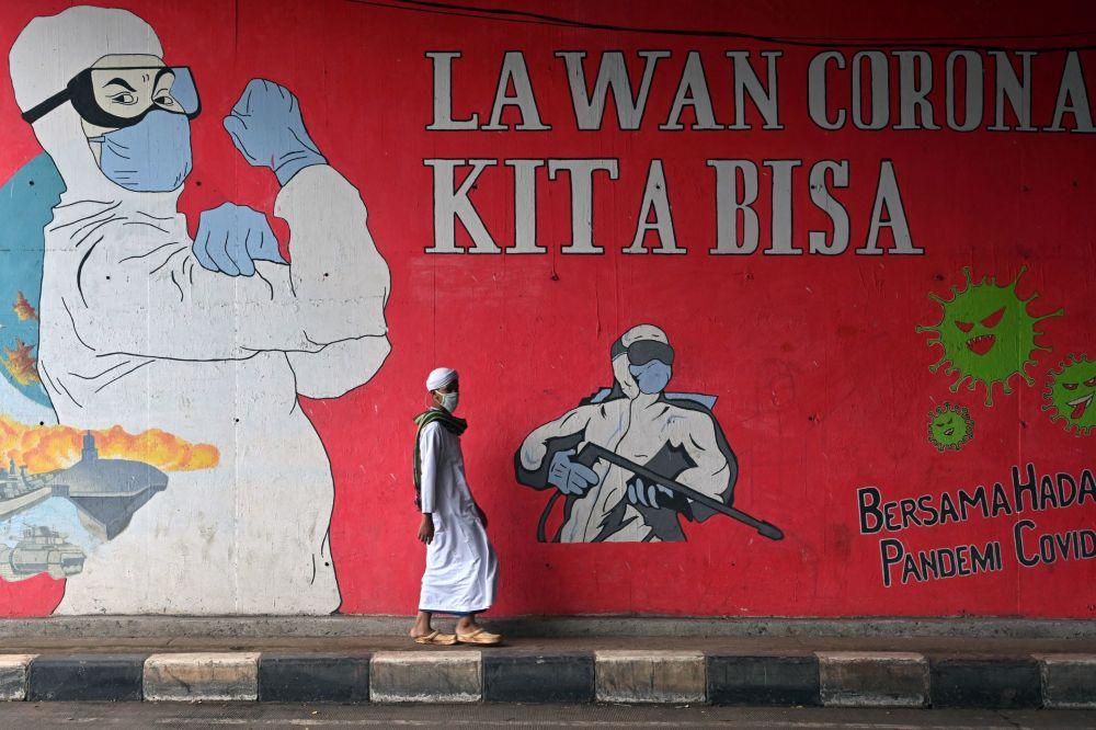 印度尼西亚雅加达,一名男子从涂鸦墙前经过。