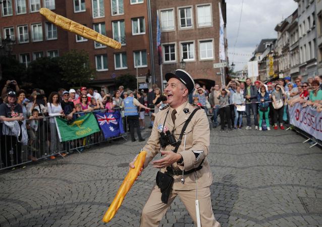 身着老式法国宪兵装的杂耍演员在活动中抛投法棍面包。