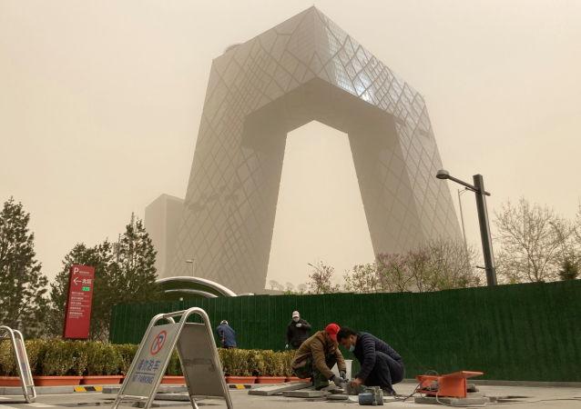 北京市民在沙尘暴天气中出行。