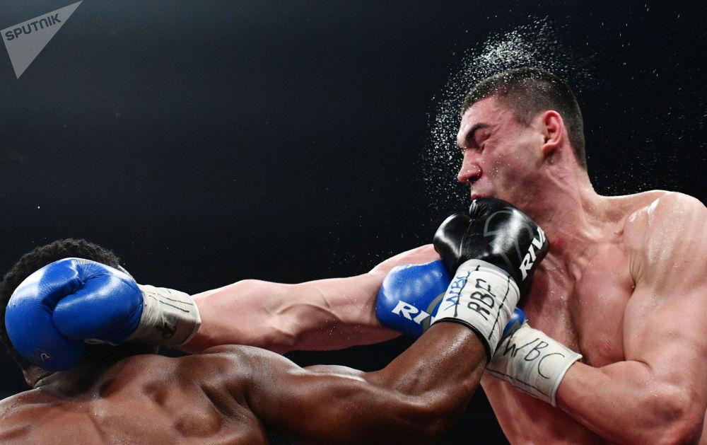 拳击运动员季先科与姆楚努在拳台上角逐。