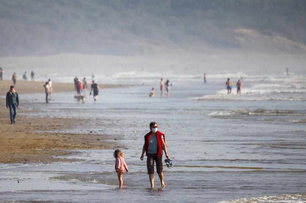 法国,晴朗天气里海滩上游玩的人们。