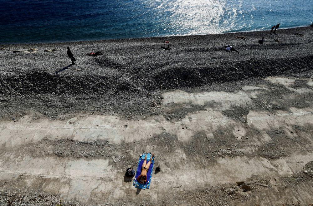 尼斯海滩上晒日光浴的女孩。