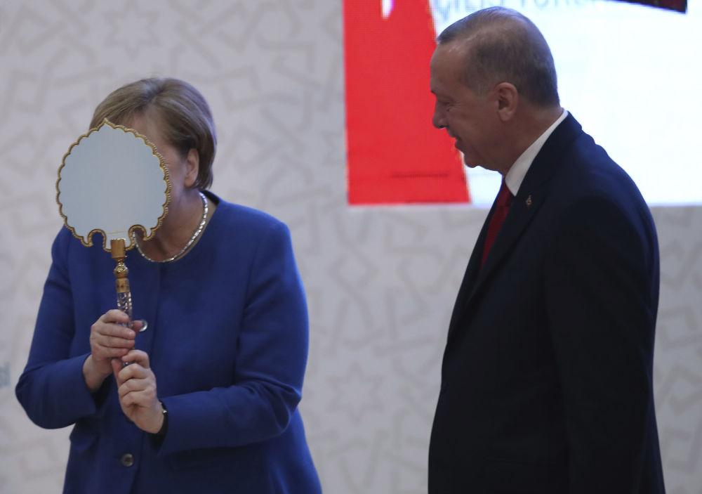2020年,德国总理默克尔在土耳其总统埃尔多安赠送的镜子前搞怪。