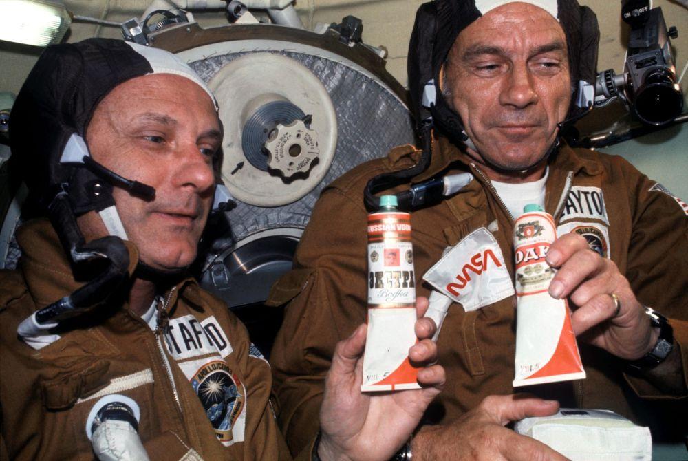 """美国宇航员托马斯·斯塔福德与唐纳德·迪克在""""联盟""""号空间站品尝苏联太空食品。"""