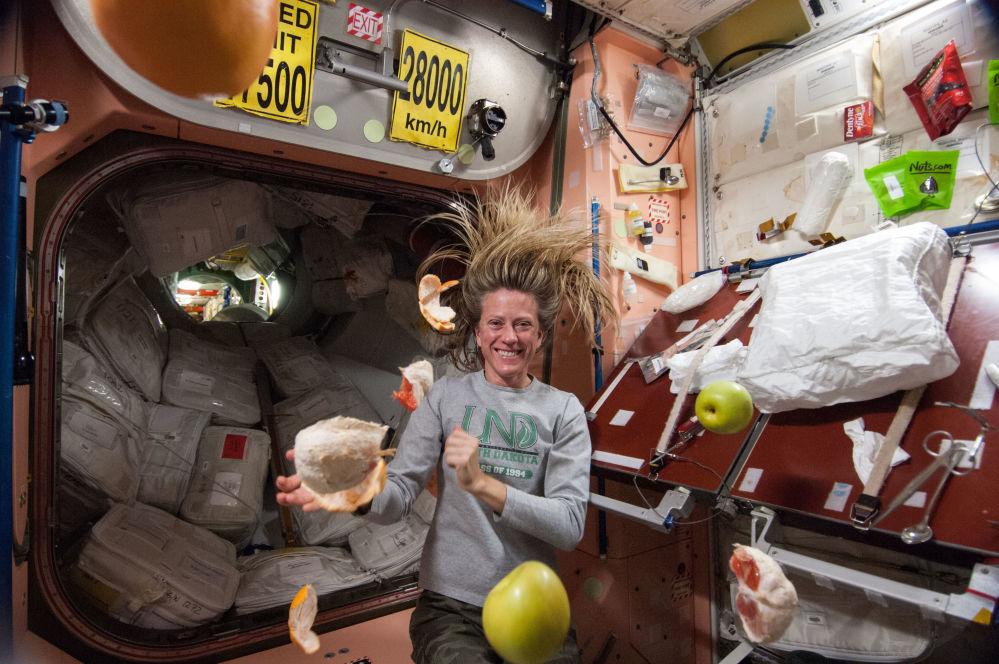 美国航天员凯伦·尼伯格在国际空间站内收集悬浮的水果。