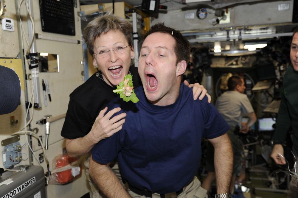 法国航天员托马·佩斯克与美国航天员威特森在国际空间站舱内就餐。