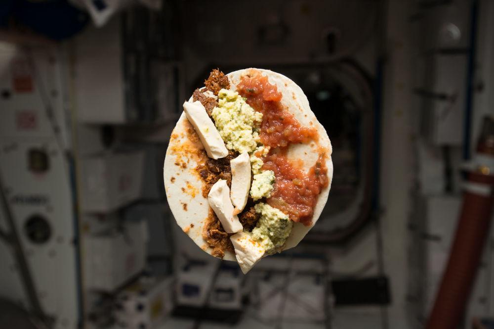 美国航天员提姆·科普拉在国际空间站内进餐。