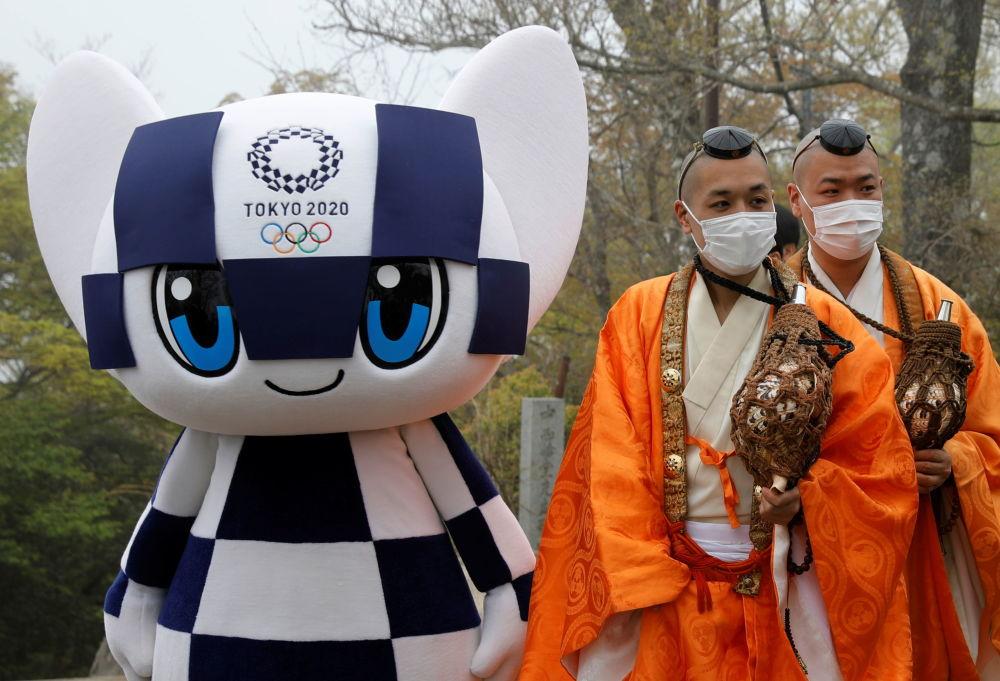 日本佛教僧人与东京奥运会吉祥物Miraitowa合影留念。