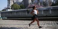 一个姑娘从巴黎圣母院前跑步经过。
