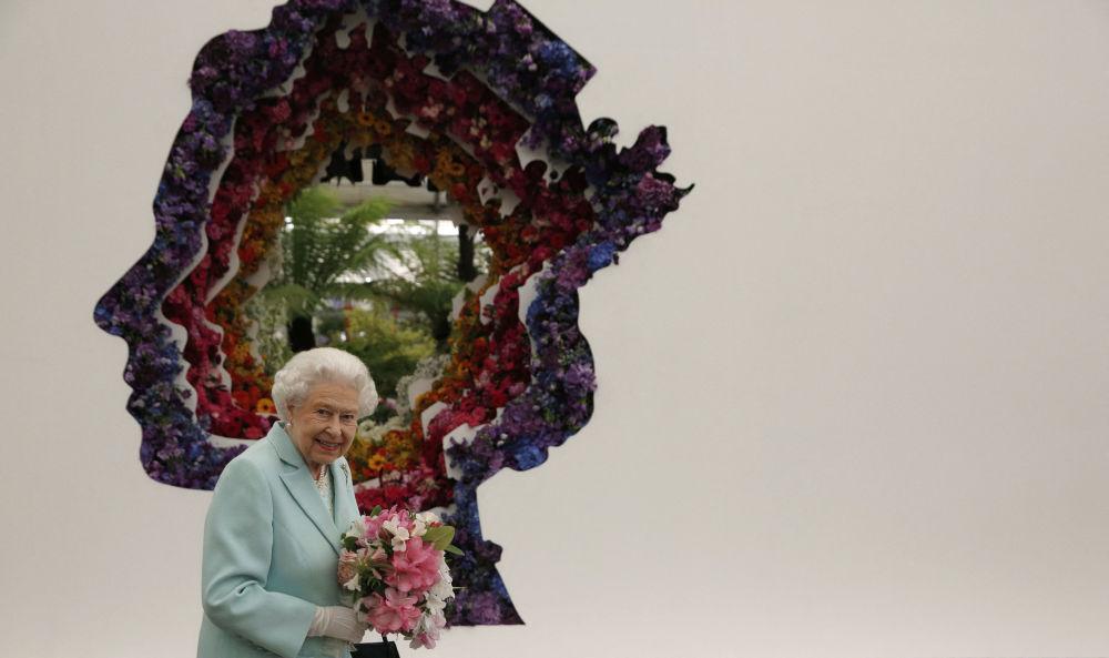 参观切尔西画展时,英女王伊丽莎白二世在她的肖像旁边。