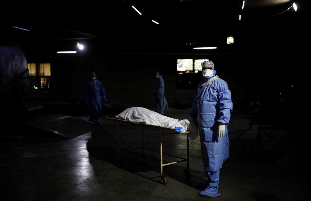 新德里医务人员正在将新冠死者推往焚尸炉。