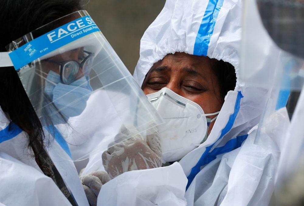 新德里居民在火葬场送别去世者家属。