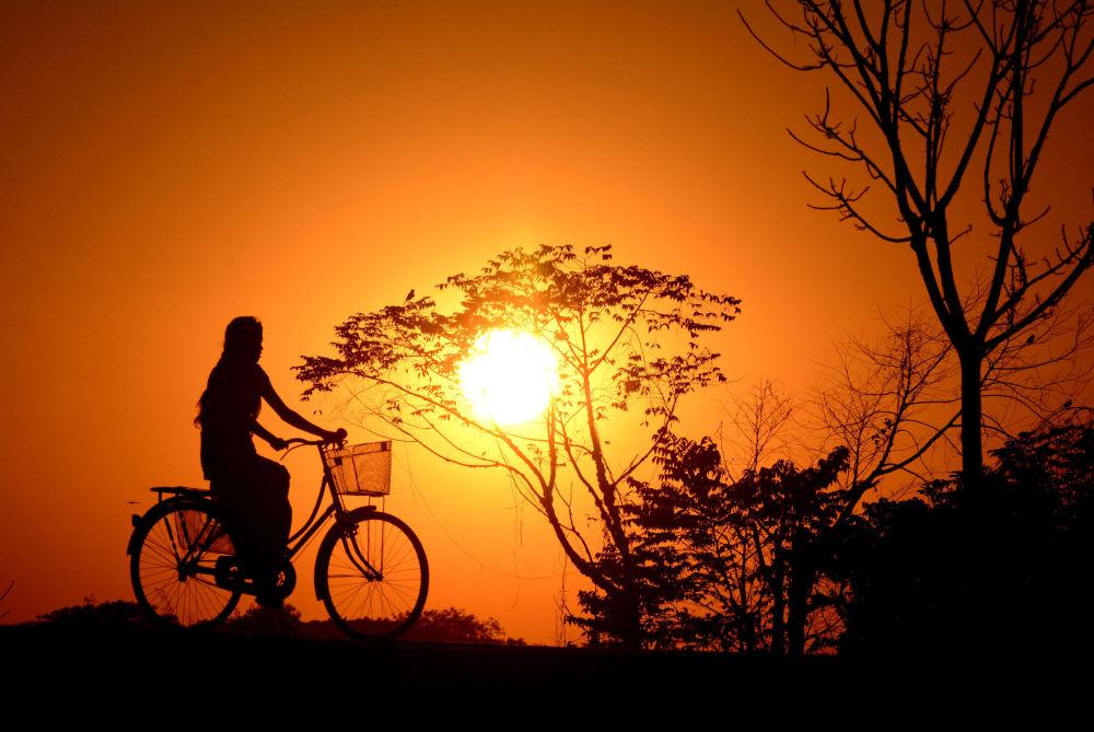 印度女孩在夕阳下骑行。