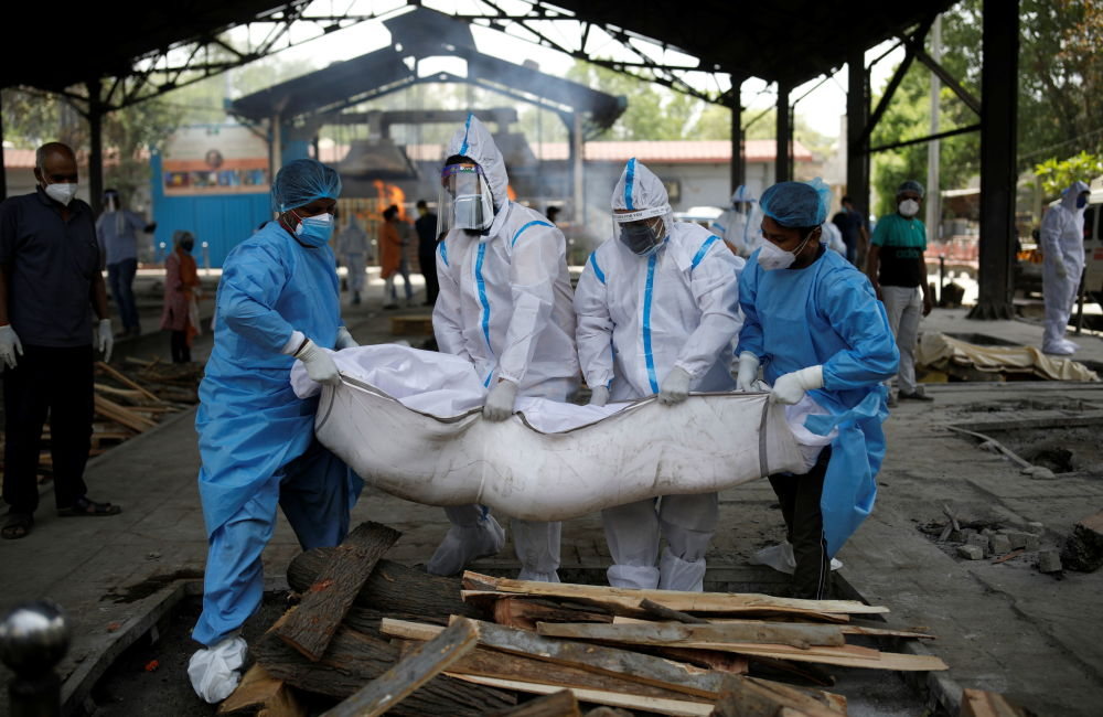 新德里医务工作者与家属搬运去世家属。