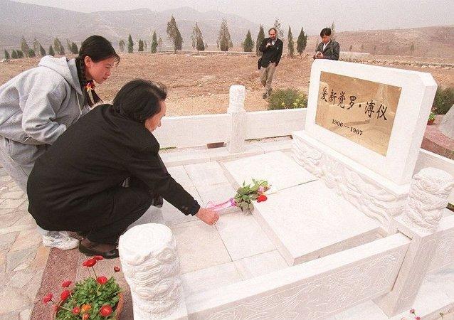 中国末代皇帝溥仪的遗孀李淑贤在他的墓前放上了鲜花