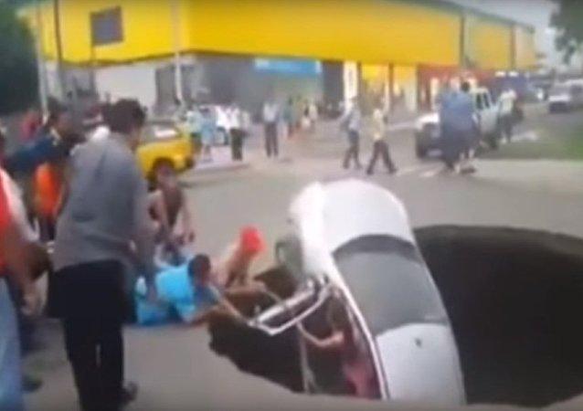 秘鲁汽车陷入地下 路人救援一家三口